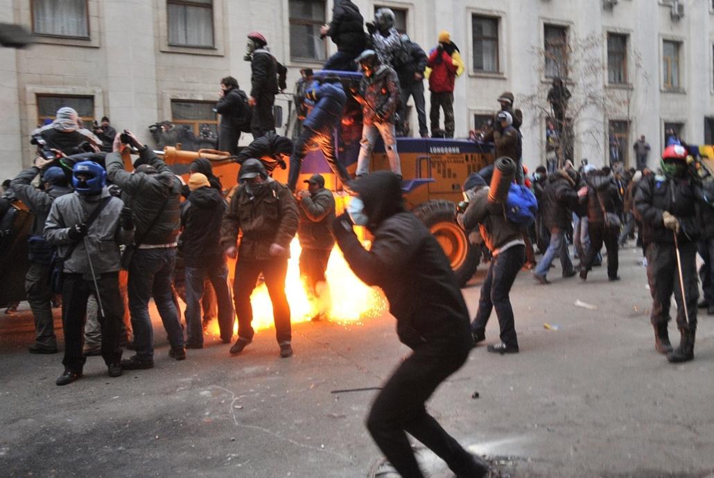afp. nagyításhoz - ne használd - ukrajna, Kijev, eu, tüntetés, A stun grenade explodes between protesters as they clash with police during the storming of the Viktor Yanukovych Presidential office in Kiev during a mass rally of the opposition in Kiev on D