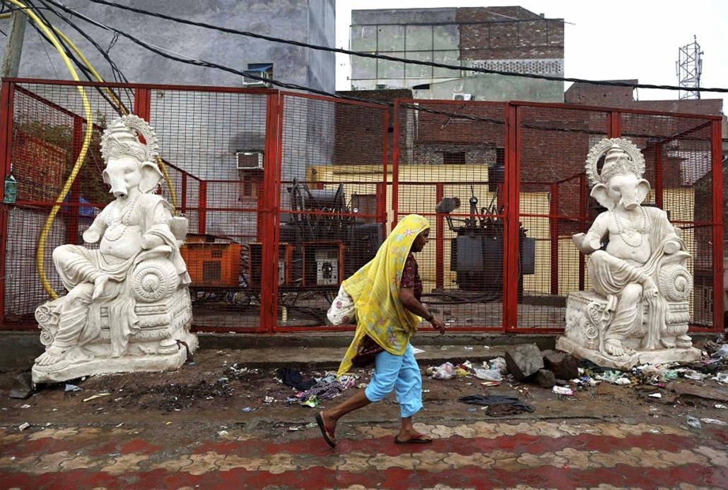 Indiai nő sétál egy transzformátortelep előtt. Az elmúlt hét súlyos áramkimaradása 670 millió embert érintett Indiában