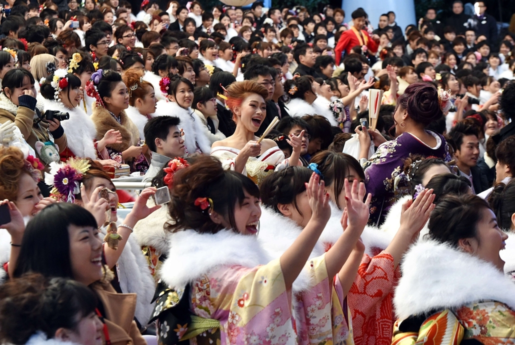 afp. Urayasu, Japán, 2015.01.12. 20-year-old women wearing kimonos watch a show by Disney characters during their Coming-of-Age Day celebration at Tokyo Disneyland in Urayasu, suburban Tokyo on January 12, 2015. The number of people aged 20 years old, the