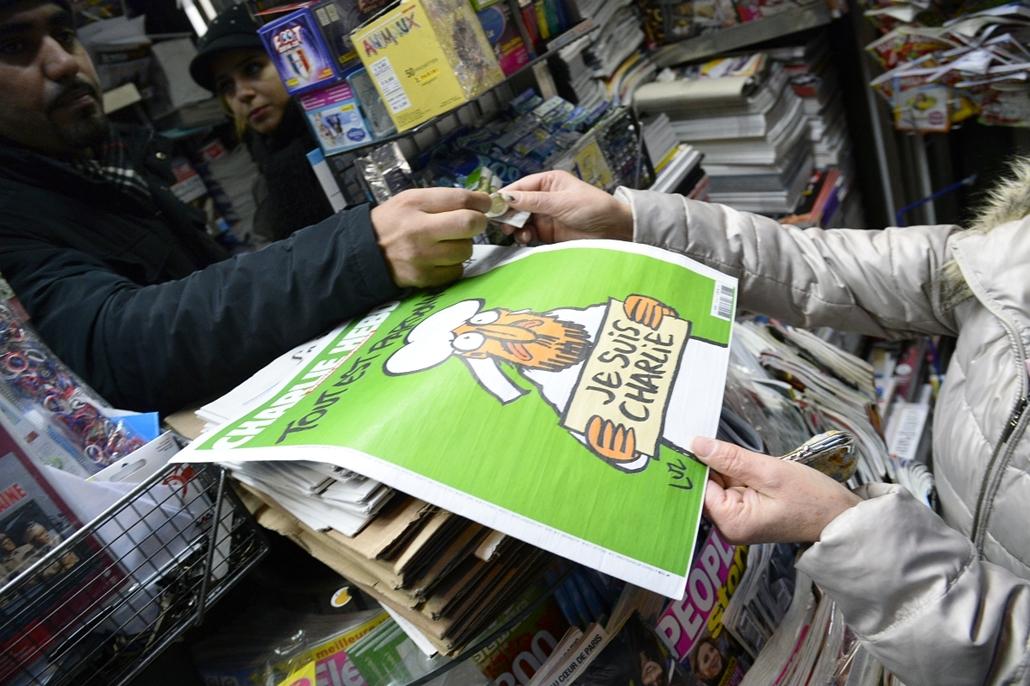 afp. Charlie Hebdo az újságárusnál, 2015.01.14. Párizs, Franciaország, párizsi mészárlás, People wait outside a newsagents in Paris on January 14, 2015 as a customer buys the latest edition of French satirical magazine Charlie Hebdo shortly after it went