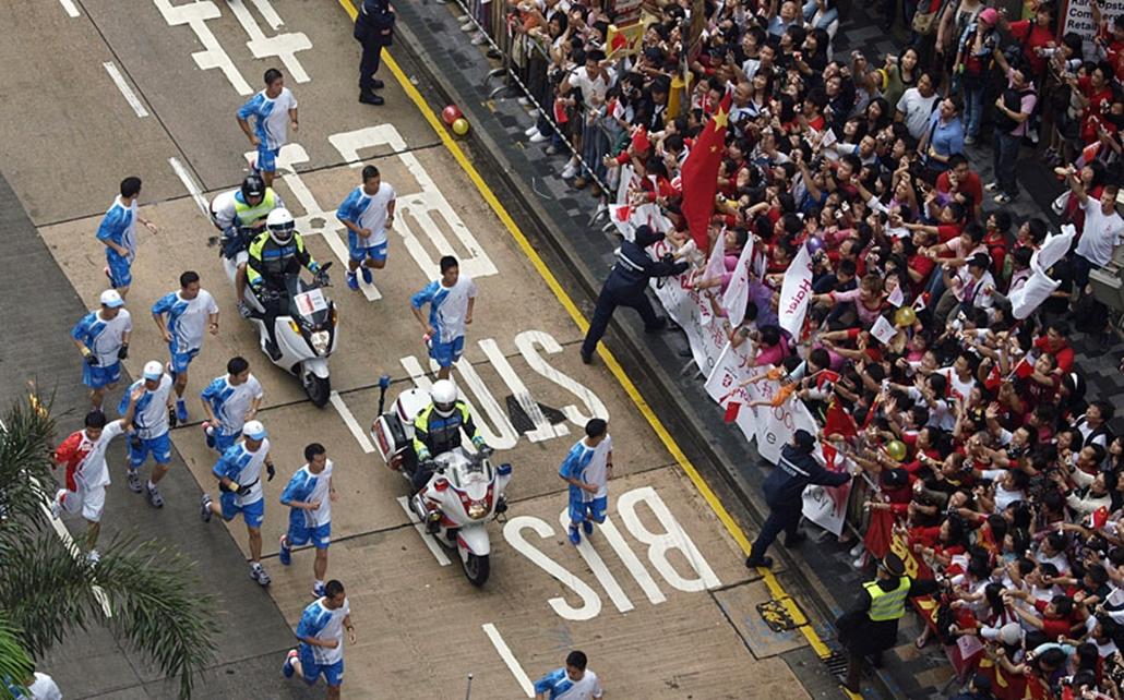 Az olimpiai lángot viszi egy futó Hong Kongban. 2008. május.