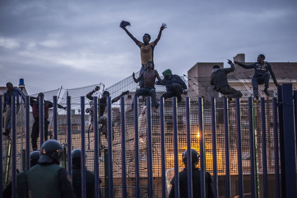 afp. hét képe - 2014.03.28. Spanyolország, Malilla - Spanish policemen watch would-be immigrants reacting on a fence near Beni Enza, into the north African Spanish enclave of Melilla on March 28, 2014. Several hundreds people launched a dawn assault today
