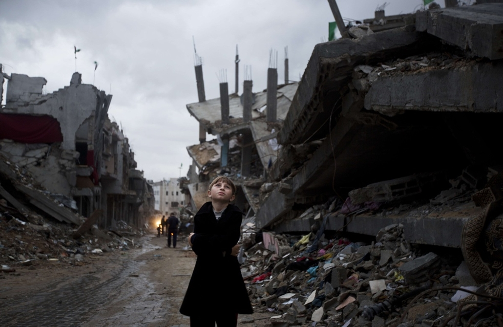 afp. hét képei - Gáza 2014.10.19. palesztin fiú, A Palestinian boy looks up during a rain storm while  walking through a neighbourhood destroyed during the 50 day conflict between Israel and Hamas, in the Shejaiya neighbourhood of Gaza City on October 19,