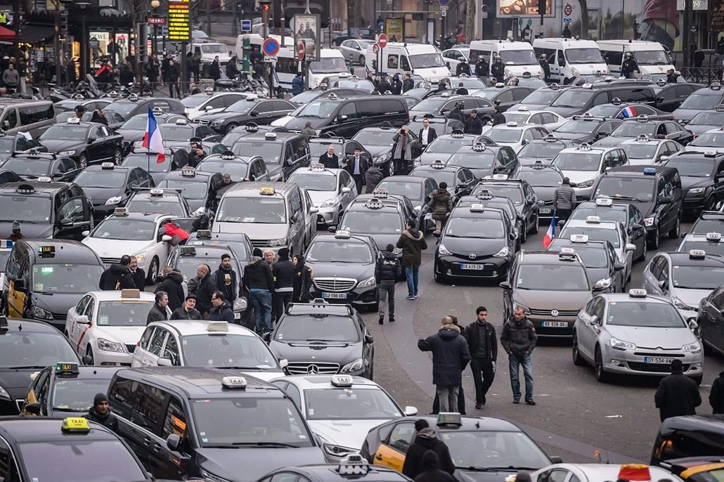 epa. 2016.01.26. Párizs, Uber, Taxistüntetés Franciaországban - Az úttesten parkolnak az Uber közösségi személyszállító szolgáltatás ellen szervezett taxistüntetés résztvevői a nyugat-párizsi Porte Maillot metrómegálló közelében 2016. január 26-án. A fran