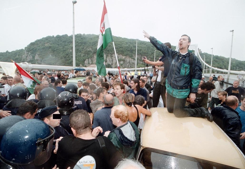tg.02.07.04. - A szavazatok újraszámlálását követelő tiltakozók torlaszolták el reggel az Erzsébet-hidat. Az előre be nem jelentett demonstráció résztvevői teljesen megbénították a forgalmat. A rendőrség megpróbálta elszállítani az autókat, de ezt a tünte
