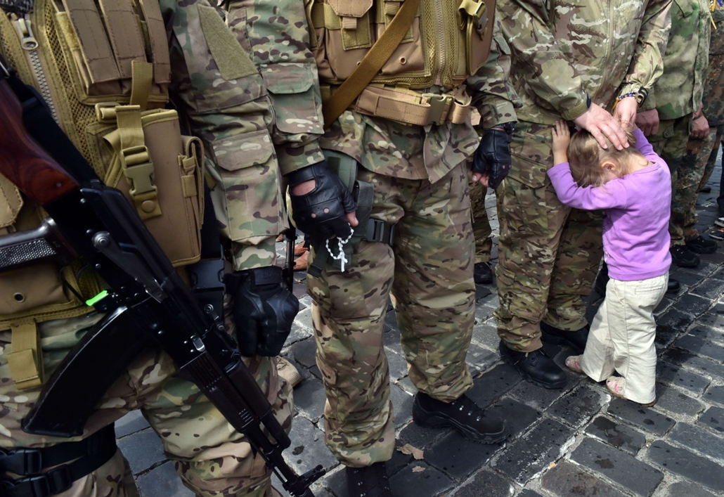 afp. Ukrajna, ukrán helyzet, Kijev, 2014.08.26. The child of a Sich special volonteer battalion member holds her father on August 26, 2014 during an oath-taking and farewell ceremony in Kiev. The battalion is leaving the Ukrainian capital to take part in