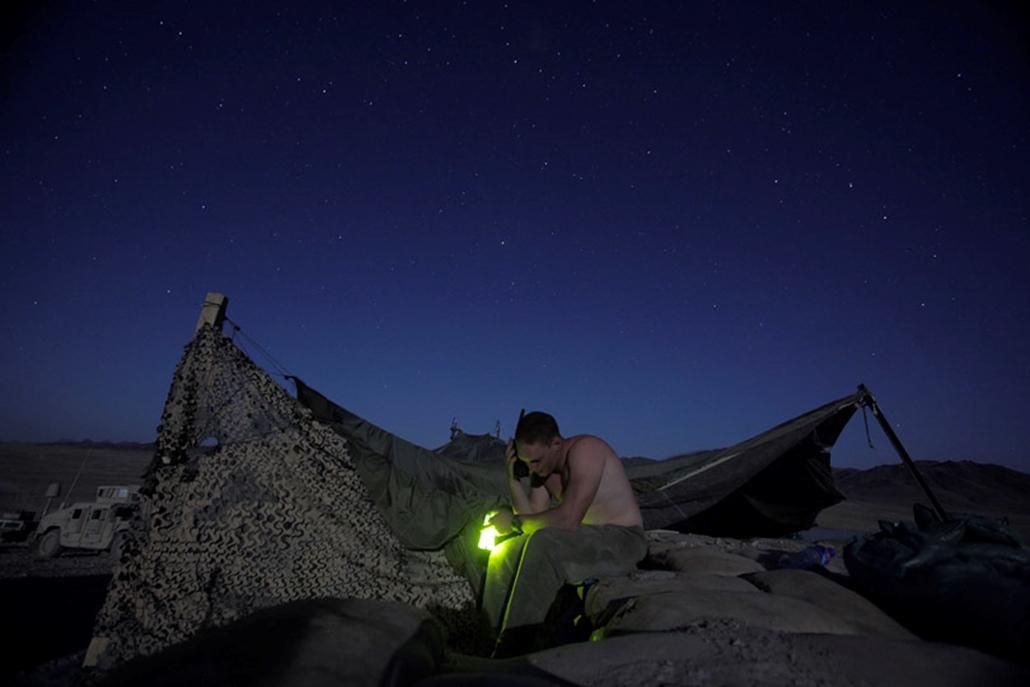 Amerikai katona a barátnőjével beszélget műholdas telefonon keresztül egy harci állásról Afganisztánban.