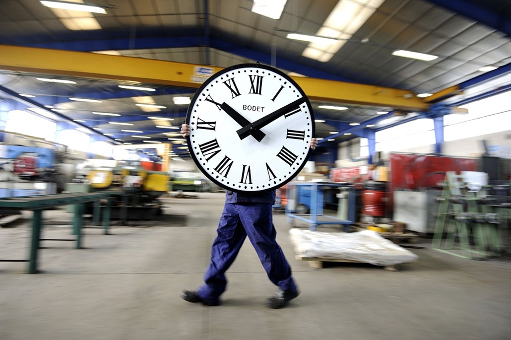 7 képei 0324-330 - Franciaország , Trémentines 2014.03.26. An employee of the Bodet Company carries a clock on March 26, 2014 at the plant of Trementines, western France. The Bodet company manufactures clocks since 1868 for churches, stations, sports hall