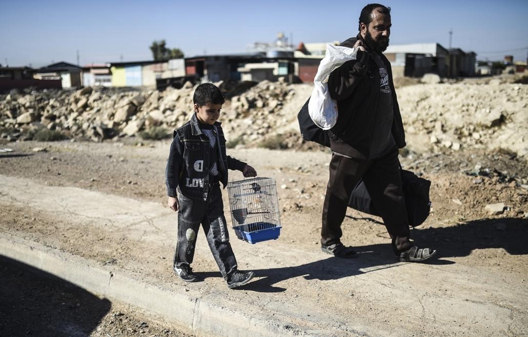 afp.16.11.03. Egy fiú édesapjával együtt elhagyja Gogjali-t, Mosul keleti részén.