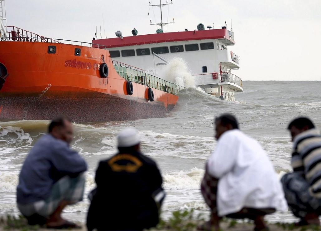 epa. Hajóbaleset Thaiföldön, Narathiwat, 2014.12.19.Zátonyta futott indonéz teherhajó helyiekkel az előtérben a Thaiföld déli részén fekvő Narathiwat tartományban 2014. december 19-én. A hajó, amely több mint 12 millió liter pálmaolajat szállított, azt kö