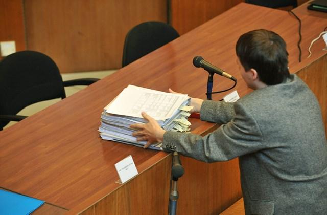 A bíróság munkatársa érkezik a tárgyalóterembe a periratokkal, mielőtt kezdetét veszi a romák elleni támadásokkal vádolt K. Árpád, K. István, P. Zsolt és Cs. István büntetőpere Budapesten, a Pest Megyei Bíróságon.