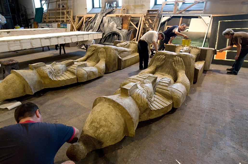 Dolgozók egy díszletként használt fáraószobrot javítanak.