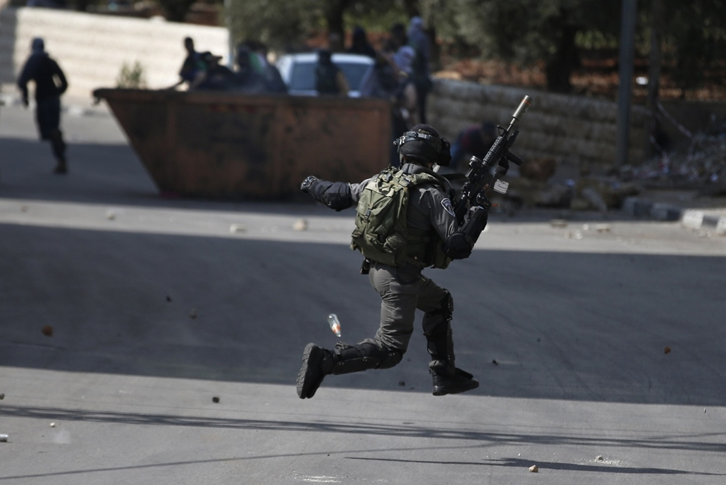 afp.izraeli-palesztin konfliktus 2015 - Beit El- 2015.10.08. Ramallah összecsapás tüntetőkkel,An Israeli security member runs as Palestinian demonstraters throw stones towards him during clashes in Beit El, near the West Bank city of Ramallah, on October