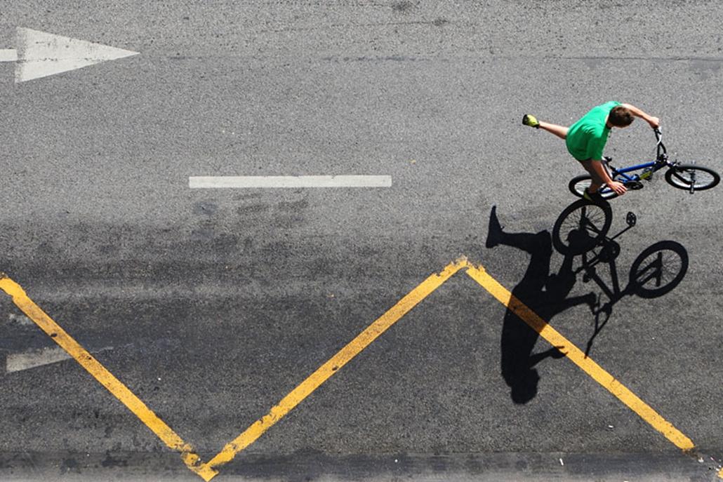 A budapesti Critical Mass előtt biciklijén gyakorol egy fiatal a szabad úttesten. 2008. április.