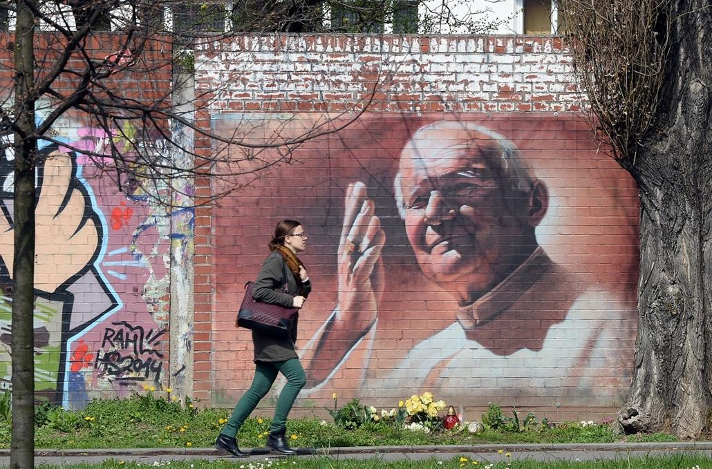 afp.2014.04.06. - Krakkó, Lengyelország: fiatal nő II. János Pál pápa portréja előtt